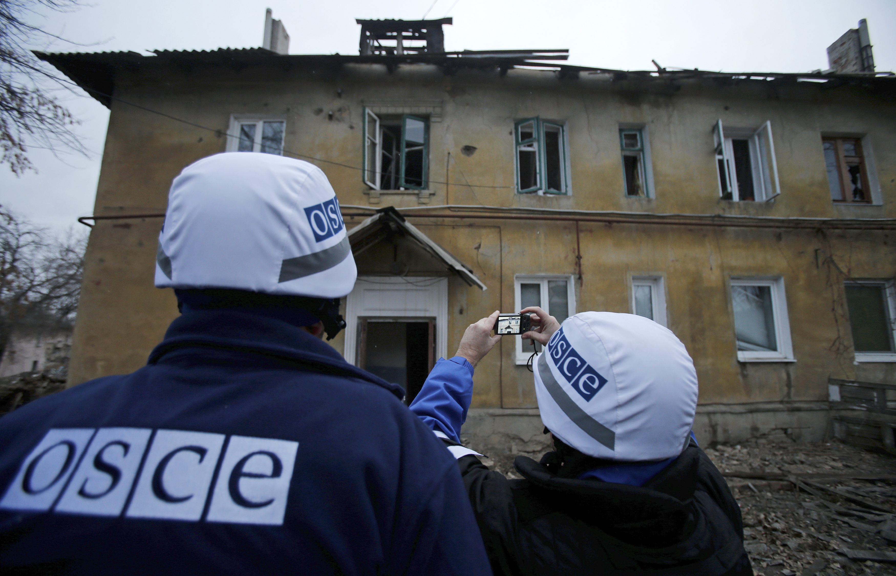 An OSCE investigator takes pictures of a building after it was damaged by recent shelling in the western part of Donetsk, eastern Ukraine