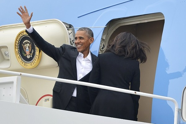 U.S. President Barack Obama waves as first lady Michelle Obama enters the door of Air Force One at Joint Base Andrews, Maryland, for their historic visit to Cuba